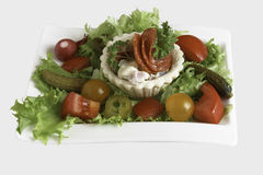 Salt tartlets with peperoni and parsley with salad, incolated on whitr background. Salt tartlets with Mayonnaise salad inside, letuce, tomato,salt cucumber Stock Image