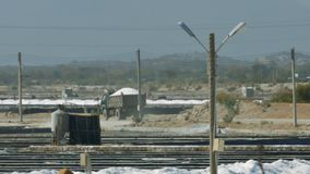 Salt Truck Drives along Road by Extraction Fields. Large truck loaded with salt drives along road past vast extraction fields and industrial construction by stock footage