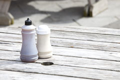 Salt and vinegar bottles on wooden table Royalty Free Stock Images