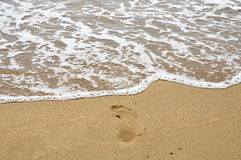 Salt water flow to foot step on the beach Royalty Free Stock Photos