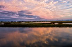 Sunset Colored Clouds with Reflection in Water. A salt water marsh in Murrells Inlet South Carolina has a beautiful sunset cloud reflection in the water. Houses Royalty Free Stock Photos