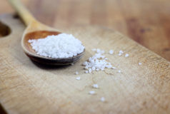 Salt in wooden spoon Stock Photos