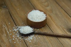 Salt in wooden spoon on wooden background stock photography