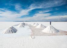 Salt worker in scenery of Salar de Uyuni in Bolivia stock photography