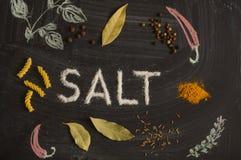 SALTA bokstäver, kryddor och örter på en svart tavla Arkivfoto