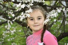 Salta en el jardín una niña que lleva a cabo una rama de la cereza. Fotografía de archivo
