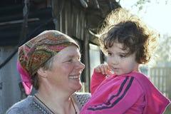Salta en los controles de la abuela del jardín la pequeña hija magnífica Fotografía de archivo libre de regalías