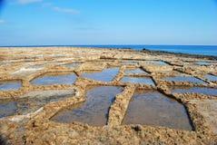 Salta pannor längs den steniga kusten utöver Xwieni skäller i Gozo Royaltyfri Bild