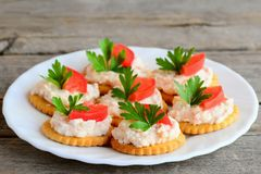 Salta smällare med gräddost på en portionplatta Enkelt mellanmål från rimmade smällare, välsmakande gräddost, nya tomatskivor Arkivbild