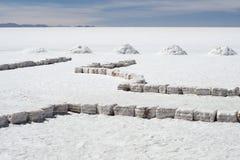 Salta tegelstenar och högar av salt på den största världs`en s saltar lägenheter Salar de Uyuni Arkivfoton