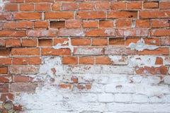 Saltado y pelando la pintura blanca en la pared de ladrillo vieja foto de archivo