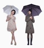 Saltan y se caen, las mujeres jovenes sonrientes con el paraguas, tiro del estudio Fotos de archivo