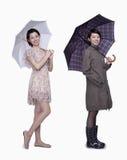 Saltan y se caen, las mujeres jovenes sonrientes con el paraguas, tiro del estudio Foto de archivo libre de regalías