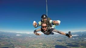 Saltando en caída libre a amigos en tándem sea feliz fotografía de archivo libre de regalías