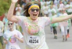 Saltando, mujer mayor feliz, sonriente cubierta con color colorido Imagenes de archivo