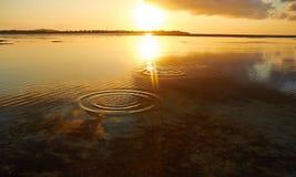 Saltando pedras no por do sol Imagens de Stock