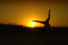Saltando per la gioia nel tramonto Immagine Stock
