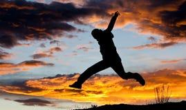 Saltando per la siluetta di gioia Immagini Stock Libere da Diritti