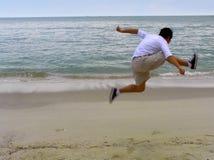 Saltando sulla spiaggia Immagine Stock