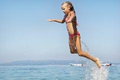 Saltar das meninas da água imagem de stock