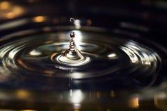 Saltar de prata da gota da água iluminada dourada foto de stock royalty free