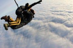 Saltar em queda livre em tandem Os Skydivers estão voando acima das nuvens brancas imagens de stock royalty free