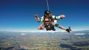 Saltar en caída libre la sonrisa en tándem de los amigos imagen de archivo