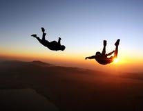 Saltar en caída libre puesta del sol sobre el mar y las montañas Fotografía de archivo libre de regalías