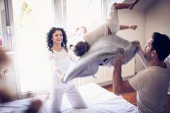 Saltar na luta da cama e de descanso com mamã e paizinho é divertimento foto de stock royalty free
