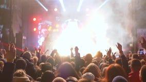 Saltar ventila com mãos acima do prazer da música ao vivo do grupo de rock na cena brilhante vídeos de arquivo