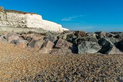 Saltdean beach seafront cliffs with boats in the background at East Sussex Brighton marina, UK stock photography