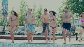 Salte en la piscina La gente joven cuenta a tres y salta en la piscina almacen de metraje de vídeo