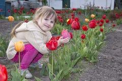 Salte en sentarse del jardín y la niña sonriente que llevan a cabo un t fotos de archivo libres de regalías