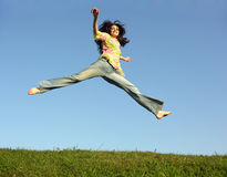 Salte a la muchacha con el pelo en el cielo Imágenes de archivo libres de regalías
