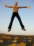 Salte a la muchacha con las hojas de otoño Foto de archivo libre de regalías