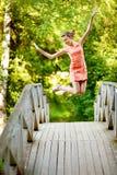 Salte a la muchacha en el puente del verano Foto de archivo