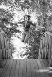 Salte a la muchacha en el puente del verano Fotos de archivo