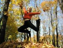 Salte a la muchacha en madera del otoño Fotografía de archivo libre de regalías