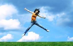 Salte a la muchacha sobre una hierba Fotografía de archivo