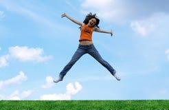 Salte a la muchacha sobre una hierba Imagenes de archivo