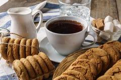 Salte las galletas, una taza de té con el limón, azúcar, vidrio de wate del hielo Fotos de archivo libres de regalías