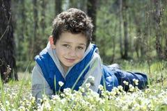 Salte nas madeiras no prado que encontra-se um menino feliz Fotos de Stock