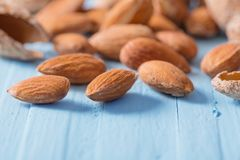 Salted almonds in shell on wooden background. The salted almonds in shell on wooden background Royalty Free Stock Photo