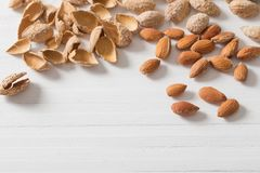 Salted almonds in shell on wooden background. The salted almonds in shell on wooden background Stock Images