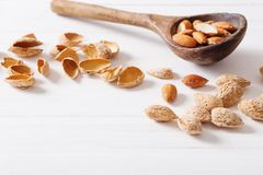 Salted almonds in shell on wooden background. The salted almonds in shell on wooden background Stock Photos