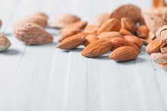 Salted almonds in shell on wooden background. The salted almonds in shell on wooden background Stock Photo