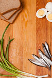 Salted anchovies, egg, bread and spring onion on wood Royalty Free Stock Images