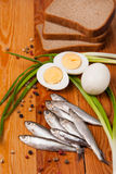 Salted anchovies, egg, bread and spring onion on wood Stock Photo