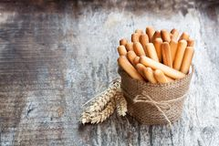 Salted bread sticks with wheat ears on wooden table royalty free stock photos