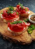 Salted bresaola beef, Italian bruschetta with soft chees, onions, whole grain mustard, chillies and fresh rosmary. Royalty Free Stock Photos